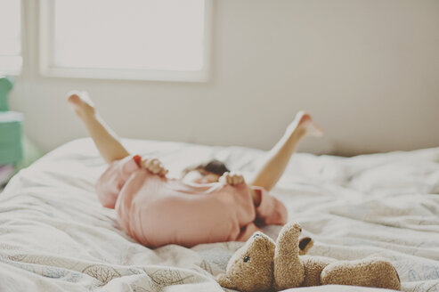 Playful girl lying on bed at home - CAVF20459
