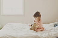 Cute girl playing with teddy bear on bed - CAVF20462