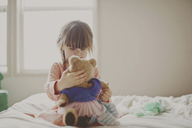 Girl playing with teddy bear on bed - CAVF20465