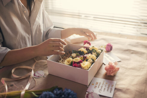 Midsection of florist arranging flowers in box - CAVF20519