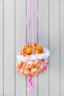 Bunch of fresh oranges in rope basket hanging against wooden wall - CAVF20648
