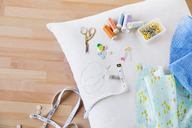 Overhead view of sewing item on pillow at table - CAVF21002