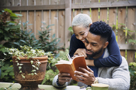 Happy woman embracing boyfriend reading book in backyard - CAVF21074