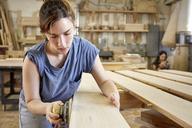 Female carpenter sanding wooden plank in workshop - CAVF21104