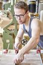 Confident carpenter working in workshop - CAVF21116