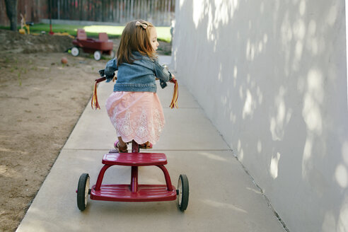 Rear view of girl riding tricycle at backyard - CAVF21395