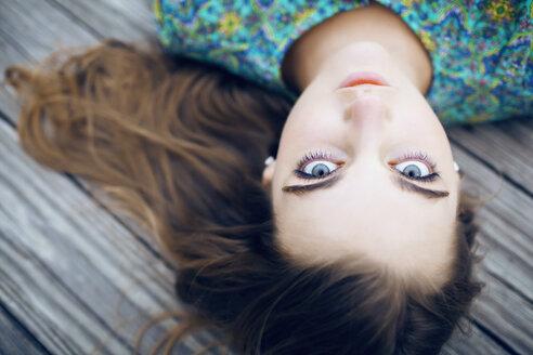 Portrait of woman lying on floorboard - CAVF21440