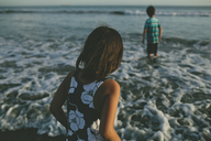 Rear view of girl with brother at beach during sunset - CAVF21476