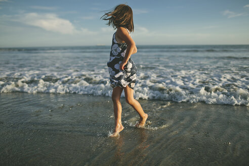 Playful girl running in sea during sunset - CAVF21479