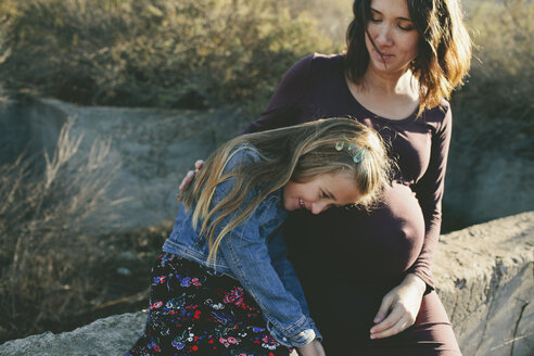 Pregnant woman looking at smiling daughter while sitting on retaining wall - CAVF21536