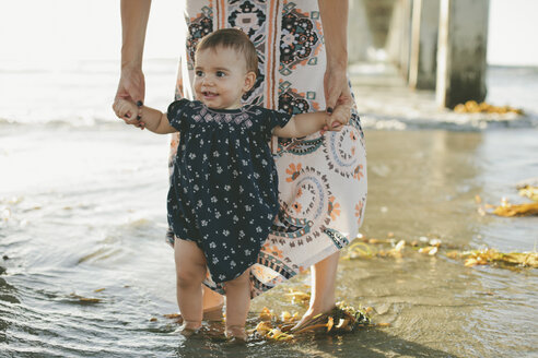 Low section of woman assisting daughter to walk at beach - CAVF21560