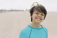 Close-up of smiling boy standing at beach - CAVF21701