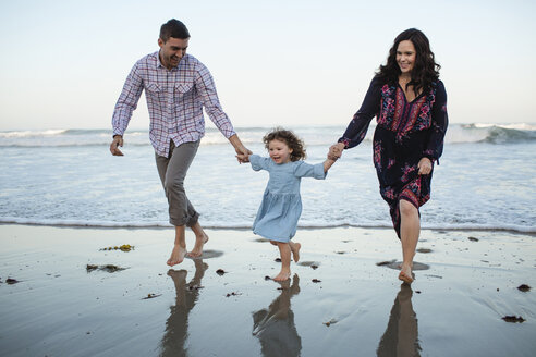 Happy daughter holding hands of parents while walking on shore at beach against clear sky - CAVF21761