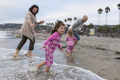 Happy family playing on shore against sky at beach - CAVF21812