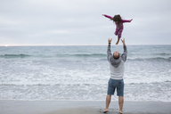 Rear view of playful father throwing daughter in air while standing on shore against sea and sky at beach - CAVF21818