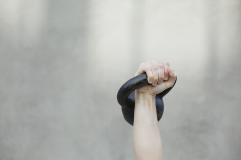Cropped hand of woman lifting kettlebell against wall while exercising - CAVF21845