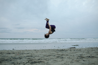 Carefree woman backflipping at beach while exercising against sky - CAVF21857