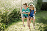 Happy siblings sitting on rope swing at front yard - CAVF21902