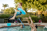 Shirtless father throwing son with inflatable ring into swimming pool with daughter in background - CAVF21911
