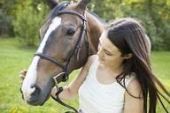 Teenage girl petting horse at field - CAVF21917