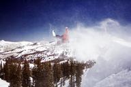 Man snowboarding on mountain against trees - CAVF21977