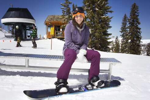Smiling woman with snowboard sitting on bench on mountain against trees - CAVF21980