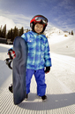 Smiling girl with surfboard standing on snow covered mountain - CAVF22013