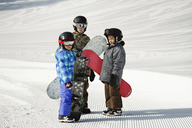 Siblings carrying snowboards while standing on snow covered field - CAVF22016
