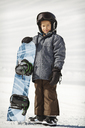Smiling boy standing with snowboard on snow covered field - CAVF22019