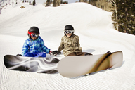 Siblings wearing snowboards while sitting on snow covered field - CAVF22022