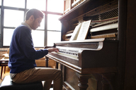 Side view of man playing piano by window at home - CAVF22070