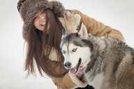 Portrait of happy woman with Siberian Husky during winter - CAVF22082