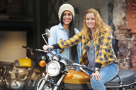 Portrait of cheerful female friends with bike outside auto repair shop - CAVF22088