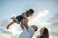 Low angle view of woman looking at father lifting son against cloudy sky - CAVF22154