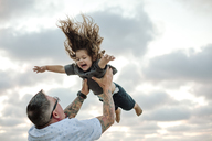 Low angle view of playful father throwing son in air while playing against cloudy sky at beach - CAVF22160