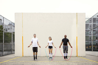 Smiling friends playing with jump ropes on street against wall - CAVF22193