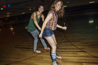 Smiling friends roller skating on roller rink - CAVF22280
