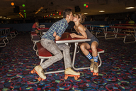 Couple wearing roller skates kissing while sitting at table in club - CAVF22283