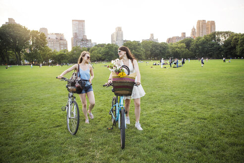 Smiling lesbian couple walking with bicycles on grassy field at park - CAVF22295