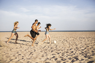 Friends playing soccer on sand at beach against sky - CAVF22313