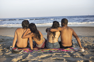 Rear view of couples sitting at beach on sunny day - CAVF22322