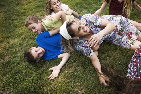 Mother enjoying with children on grassy field at park - CAVF22376