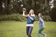 Female friends playing football on grassy field - CAVF22415