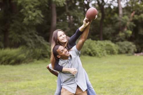 Man piggybacking woman while playing football on field - CAVF22436