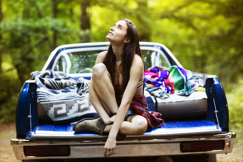 Thoughtful woman sitting in pick-up truck at forest - CAVF22466