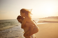 Side view of couple enjoying piggyback ride at beach during sunset - CAVF22487