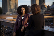 Female friends talking while standing by railing at Brooklyn Bridge during sunset - CAVF22538