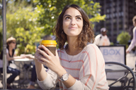 Thoughtful woman holding disposable coffee cup at sidewalk cafe - CAVF22547