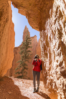 Hiker photographing while standing by rock formations at Bryce Canyon National Park - CAVF22568