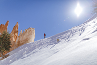 Low angle view of hiker walking on snow covered mountain against sky during sunny day - CAVF22571